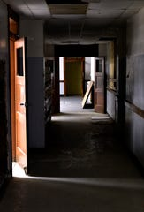 Shadows and pools of light illuminate a hallway in the former Lincoln Middle School.