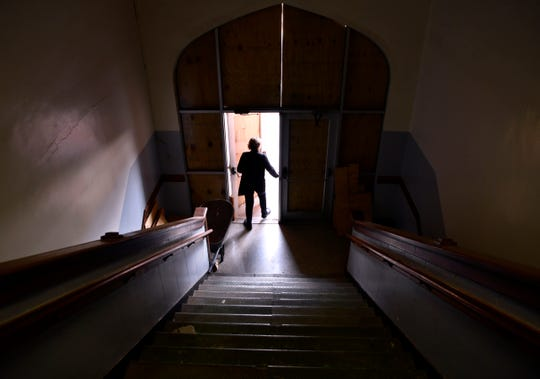 Janis Test walks out the main entrance to the former Lincoln Middle School at the conclusion of a building tour Tuesday.
