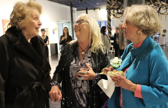 Exhibiting artist Kathie Walker-Millar, center, shares a laughs with friends attending a reception Feb. 22 at The Center for Contemporary Arts.