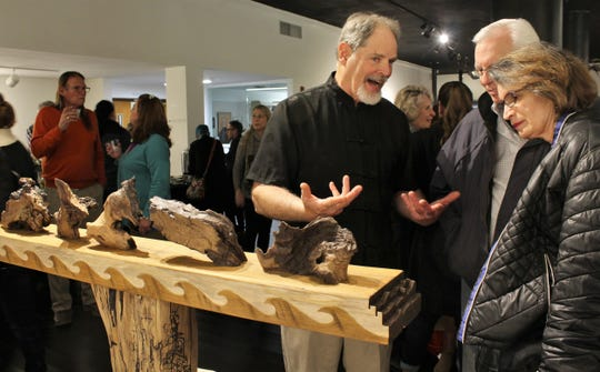 "Larry Millar, center, describes wood that has artistic appeal and is presented as art in his exhibit that's part of the ""Full Tilt Tea Party"" at The Center for Contemporary Arts. The middle of five pieces, he said, look likes a chicken."