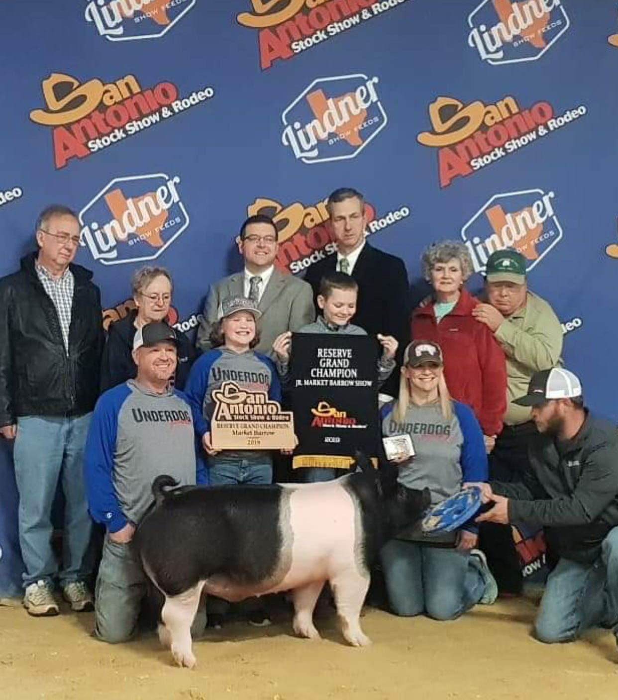 Logan Malone, holding the reserve grand champion banner Feb. 21, is surrounded by friends and family - as well as his cross hog, Tequila - at the San Antonio Stock Show & Rodeo.