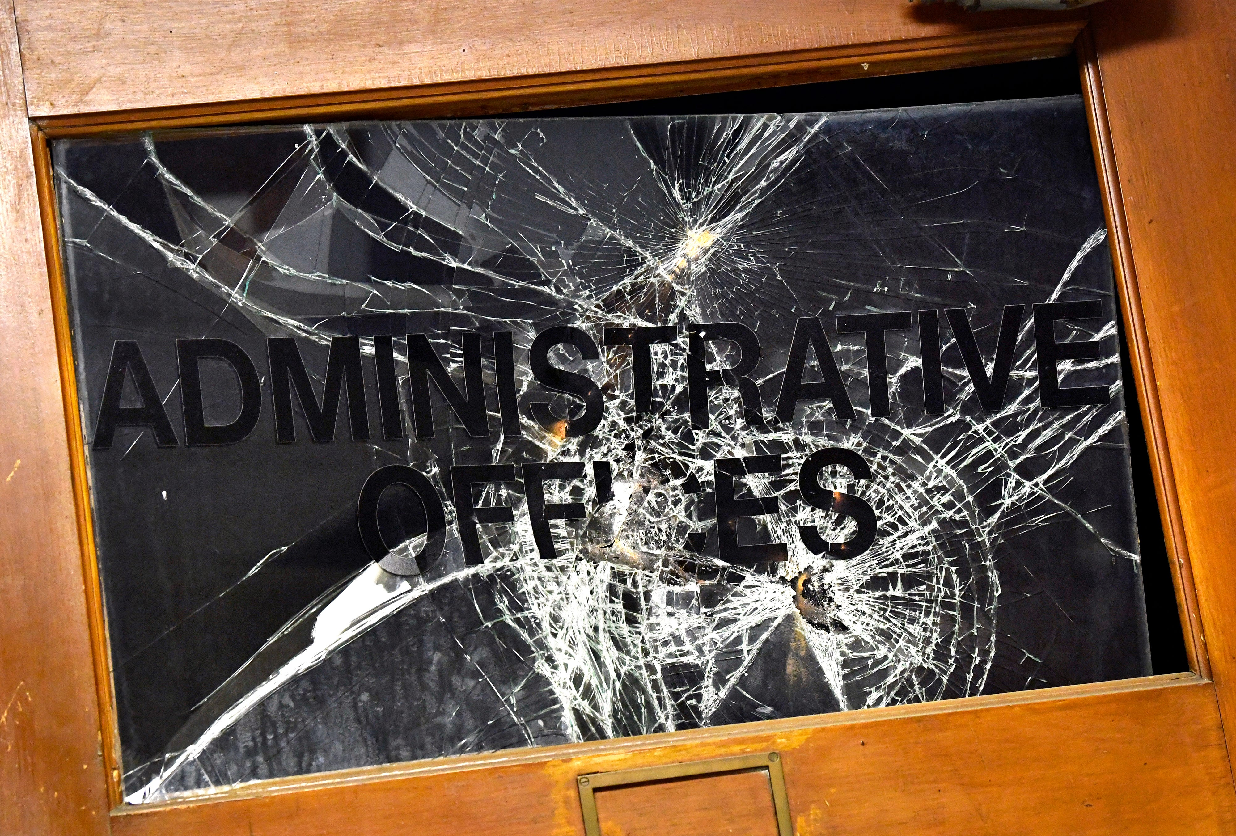 The glass on the administrative offices door at the former Lincoln Middle School. Graffiti and spray paint, as well as other damage, are spread intermittently throughout the 96-year-old building.