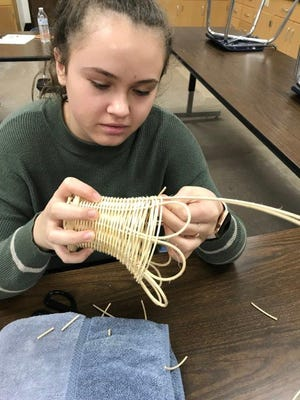 Paige Smith puts the finishing loops on the final row of her basket, which waswoven during the February meeting of the Nuts About Nature Junior Gardeners.