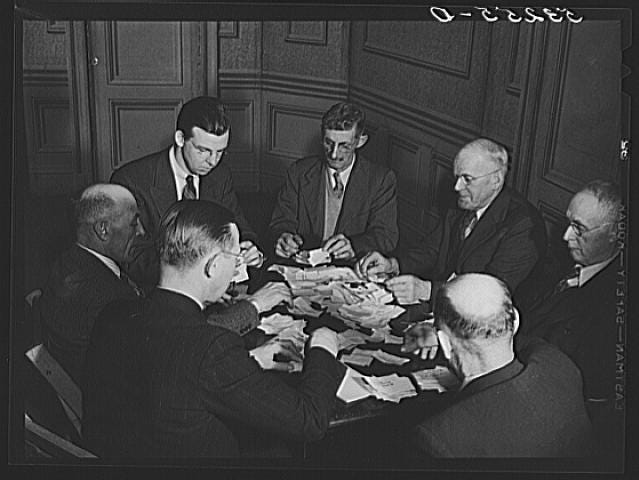 Men gather around a table on Town Meeting Day in Woodstock, Vermont. Photograph created/published March 1940. Photographer Marion Post Wolcott, 1910-1990.