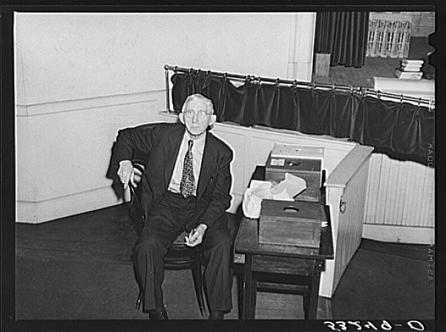 Woodstock, Vermont's former sheriff takes his lunch during a break on Town Meeting Day and guards the ballot boxes. Photograph created/published March 1940. Photographer Marion Post Wolcott, 1910-1990.