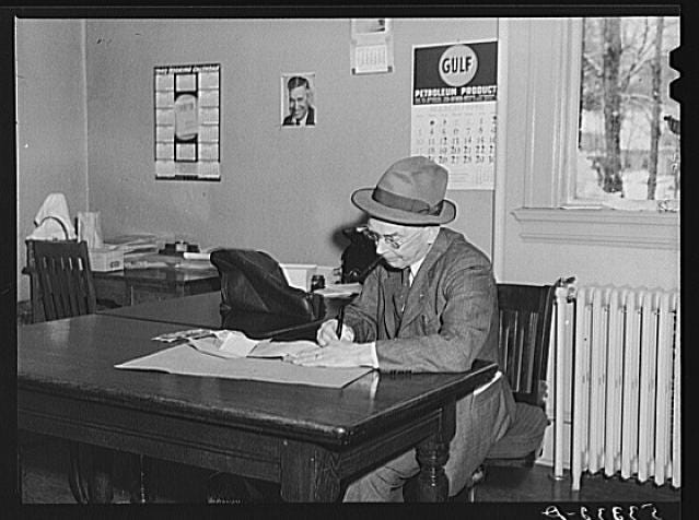 The town treasurer is pictured sitting in his office on Town Meeting Day in Woodstock, Vermont. Photograph created/published March 1940. Photographer Marion Post Wolcott, 1910-1990.