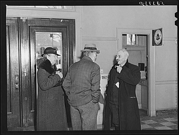 People talk in the hallway on Town Meeting Day in Woodstock, Vermont. Photograph created/published March 1940. Photographer Marion Post Wolcott, 1910-1990.