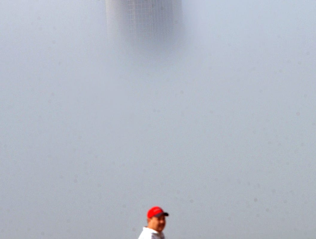 A father and his child walk through Cole Park while fog obscures everything but the top of One Shoreline Plaze in downtown Corpus Christi on March 12, 2003.