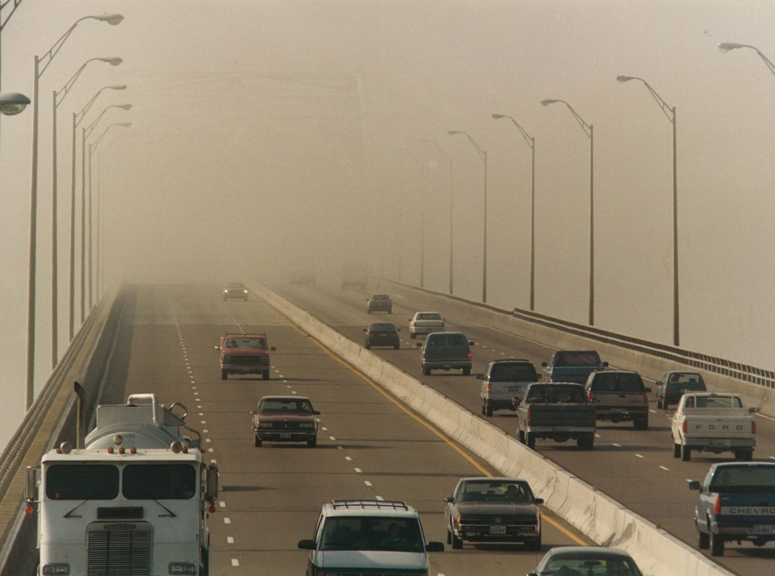 Motorists disappear into the fog covering the top of the Harbor Bridge in Corpus Christi on Jan. 24, 1994.