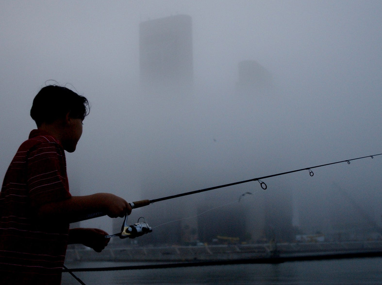 Tammie Rodela (left), 13, and her cousin Roger Garza (cq), 10, fish off the Peoples St. T-Head on a foggy afternoon in Corpus Christi on Jan. 9, 2005.
