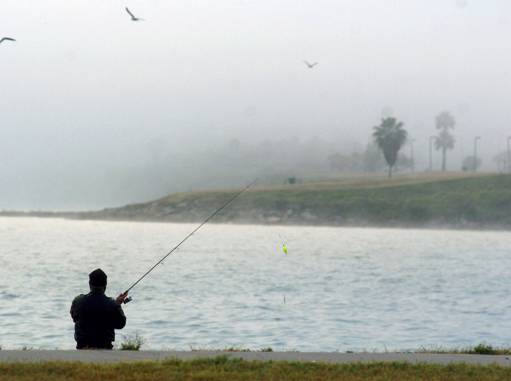 A thick, early morning fog starts to break up along the bay as Joe Davenport of Corpus Christi recasts his line into the water Tuesday, Dec. 25, 2007, along Cole Park in Corpus Christ. Davenport, who tries to get out and fish as much as he can, said the darkness a thick fog creates can sometimes keep the fish around a little longer in the mornings.