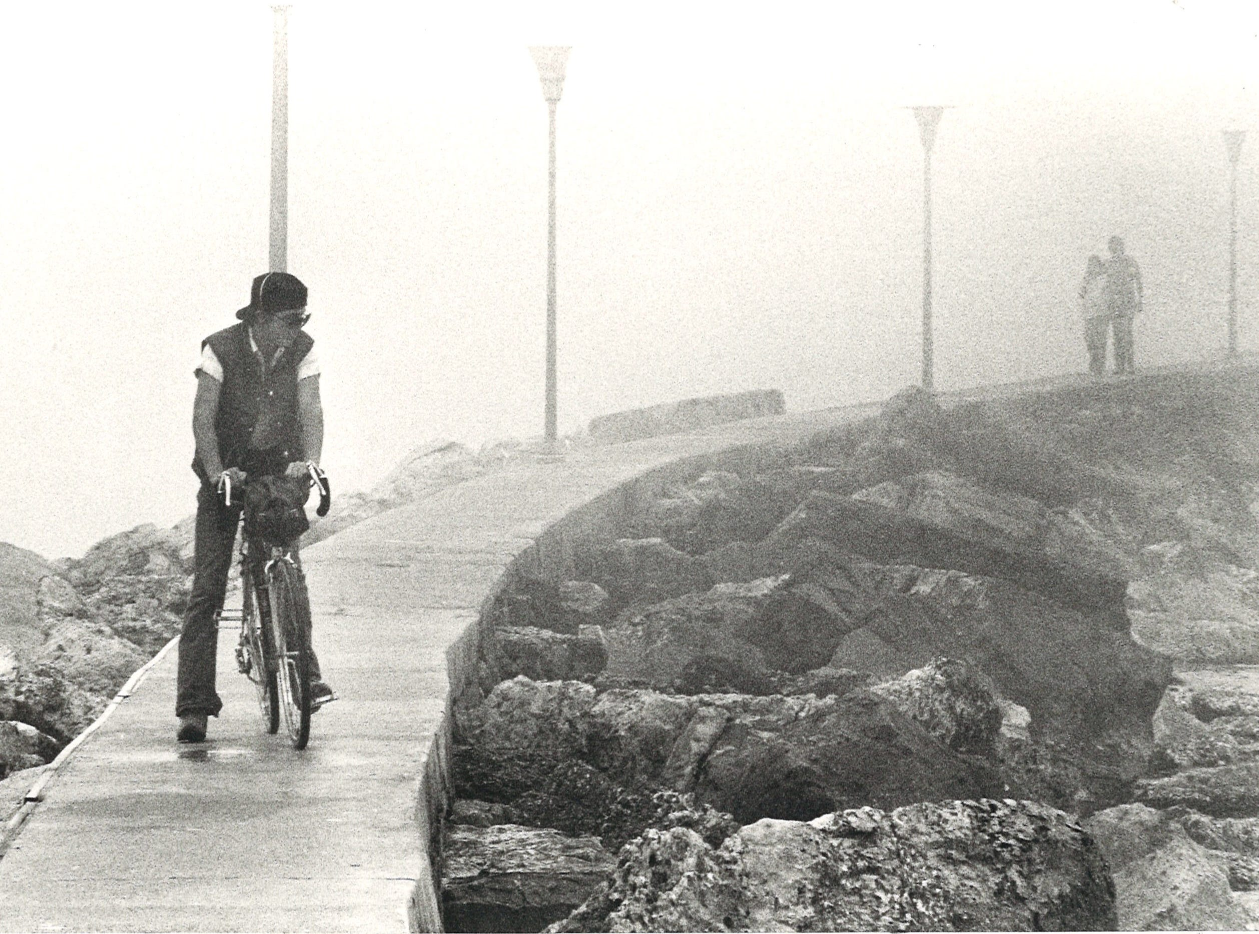 Jerry William Smith (on bike) rides along the sidewalk of the breakwater in Corpus Christi Bay on Jan. 8, 1984 as Glen and Judy Kreais stroll in the fog.