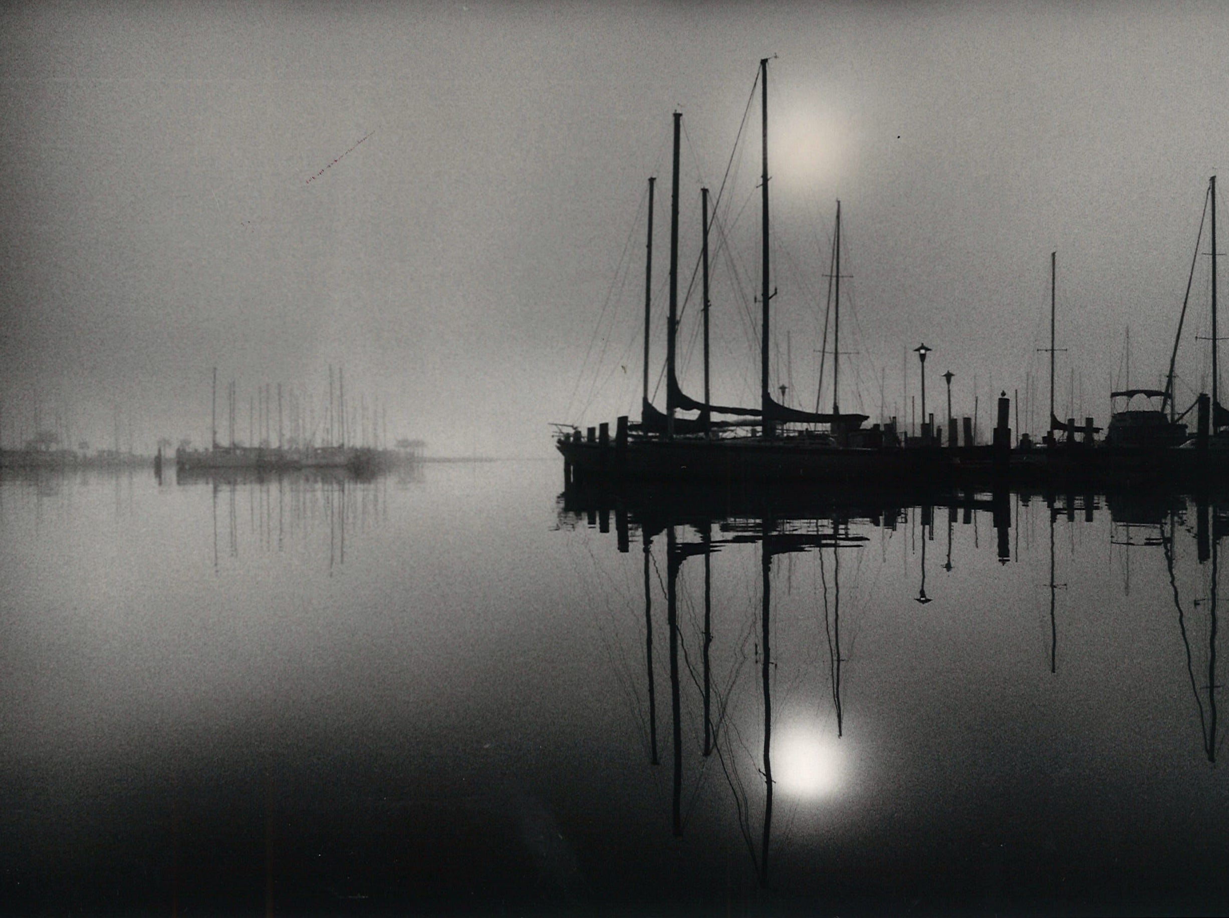 The sun tries to break through the morning fog on Corpus Christi Bay on Nov. 18, 1986. The Lawrence Street T-head is on the left and the Coopers Alley L-head on the right.