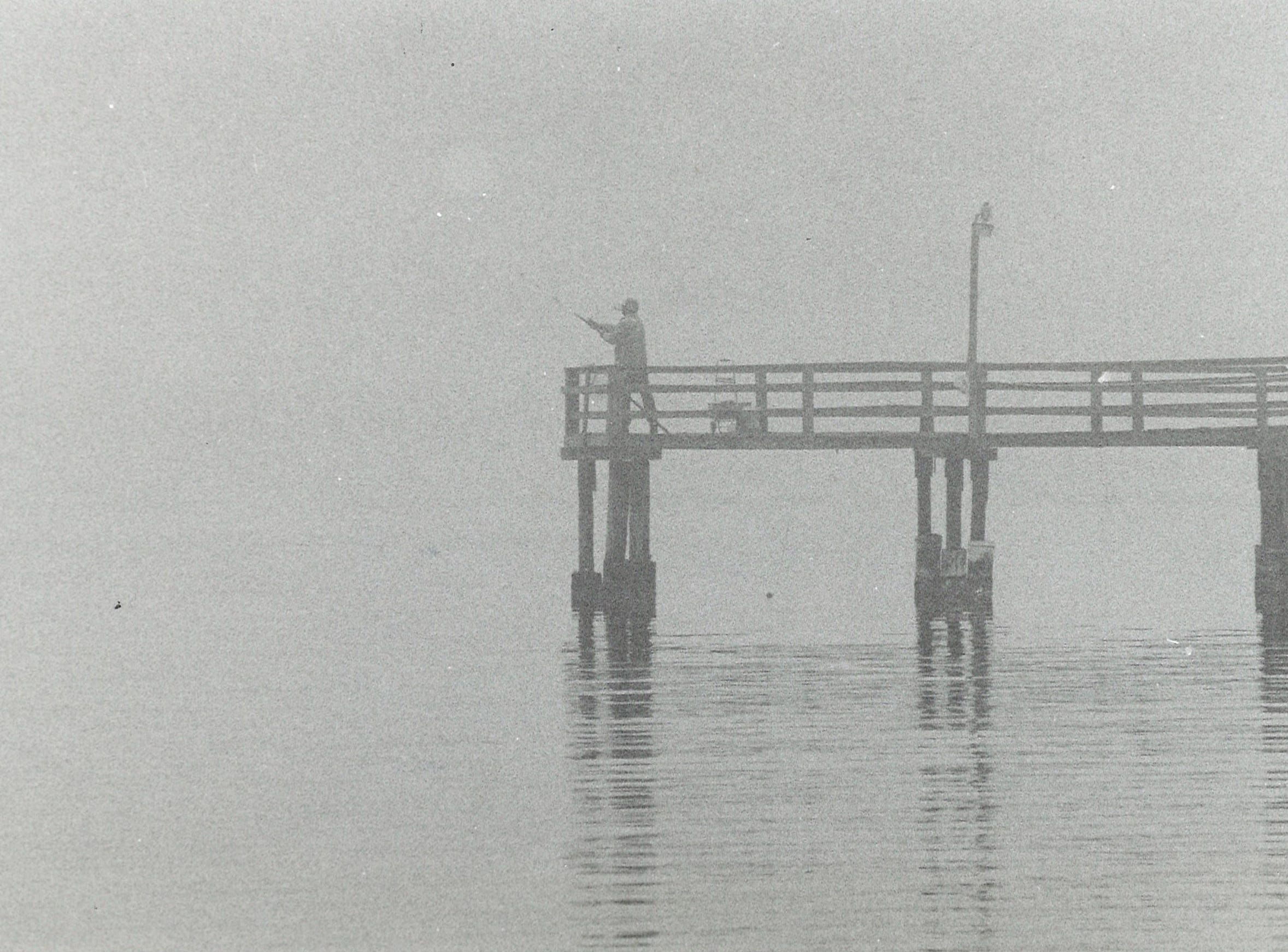 A fisherman braves the heavy fog that blanketed Corpus Christi Bay as he casts off from Oso Pier on Nov. 11, 1994.