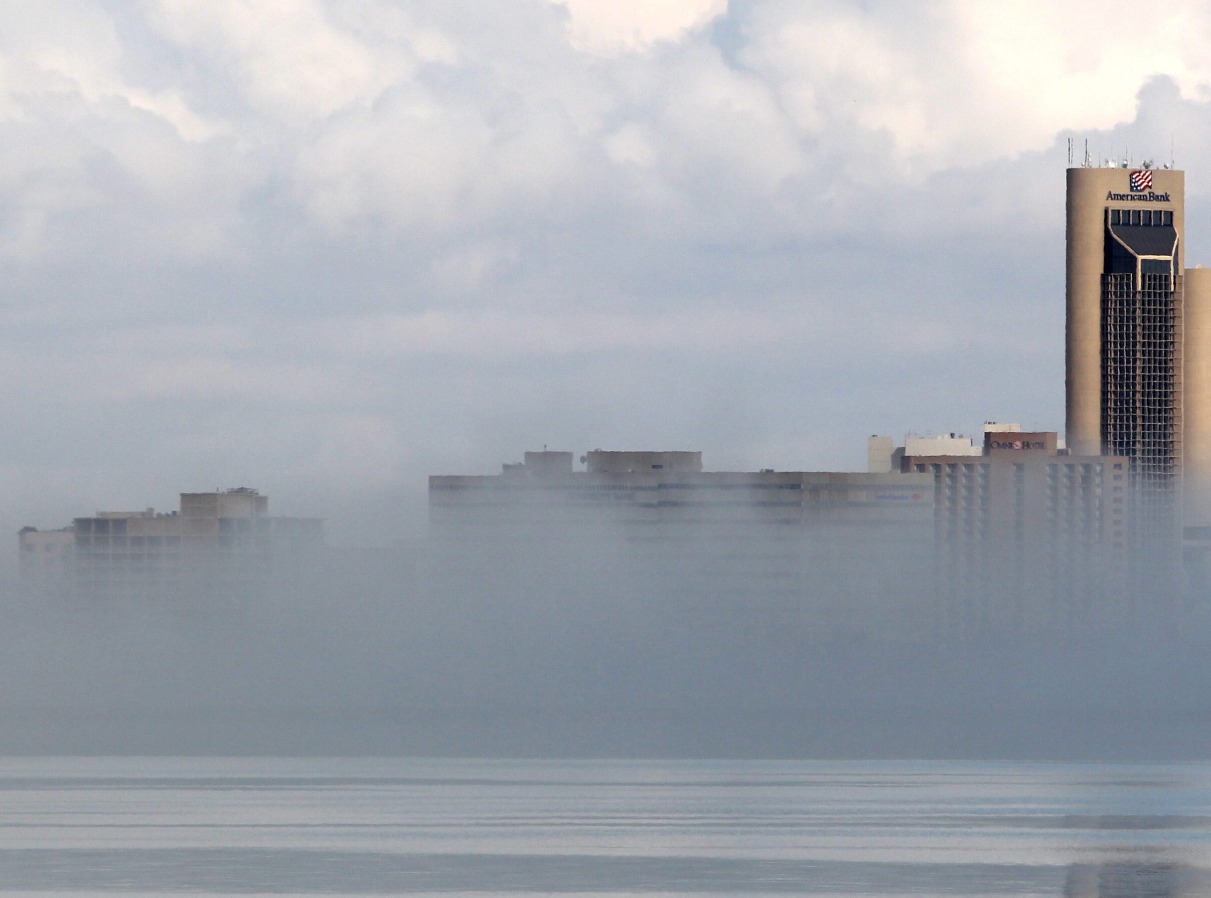 Only the tops of buildings along Shoreline Boulevard can be seen as fog blanketed downtown Corpus Christi March 25, 2014.