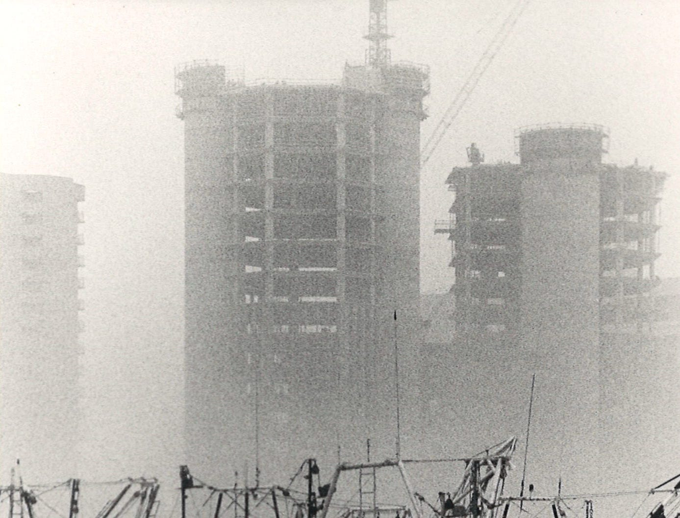Shrimp boats in the fog at the Peopls St. T-head in Corpus Christi on Jan. 15, 1987. In the background, One Shoreline Plaza is under construction.