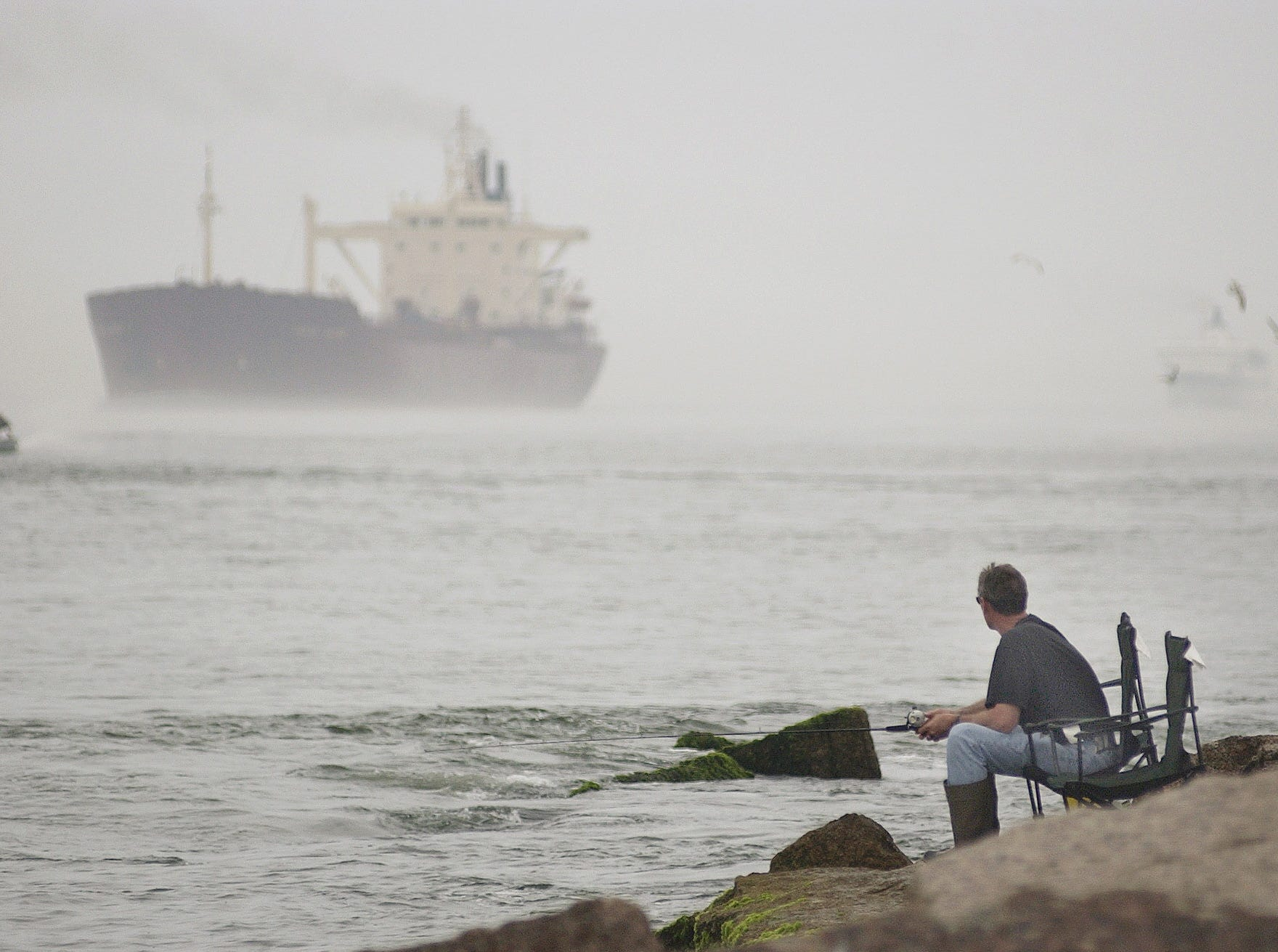 Dion Hodge from New Braunfels, fishes along the Port Aransas jetty as two large ships pass through the fog to come in to port on March 13, 2003.  The first ship is the Tanja Jacob and the second ship is the Texas Treasure.