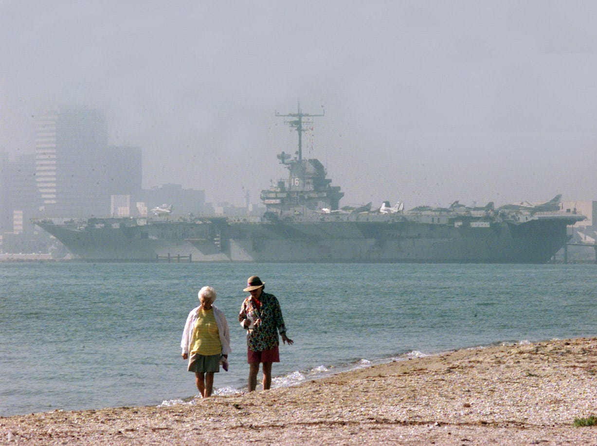 Some early risers walk past the Lexington Museum on the Bay in foggy conditions Feb. 8, 2000 on Corpus Christi Beach.