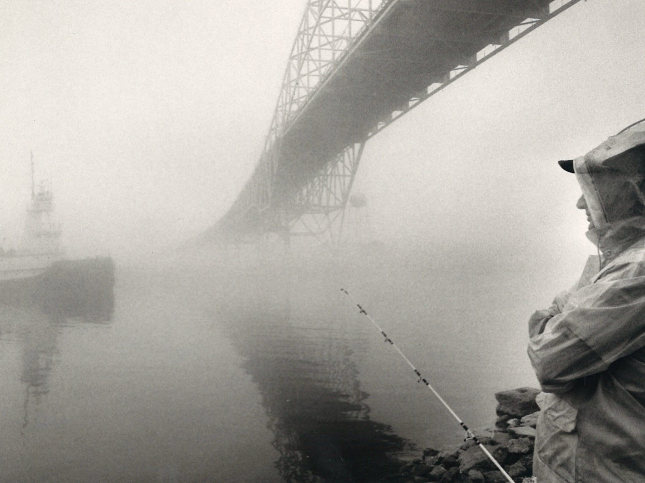 Bob Madison watches a tug boat manuever through the dense fog as he fishes under the Harbor Bridge in Corpus Christi on Jan. 30, 1985.