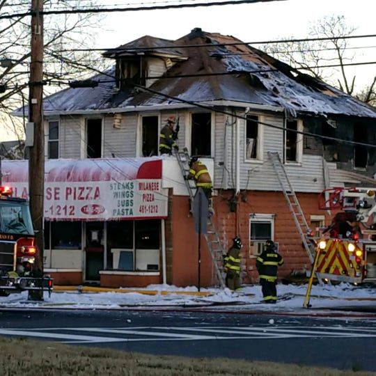 Firefighters remain on the scene of a fire above Milanese Pizza in Delran Tuesday morning, hours after responding to an intense blaze at the building.