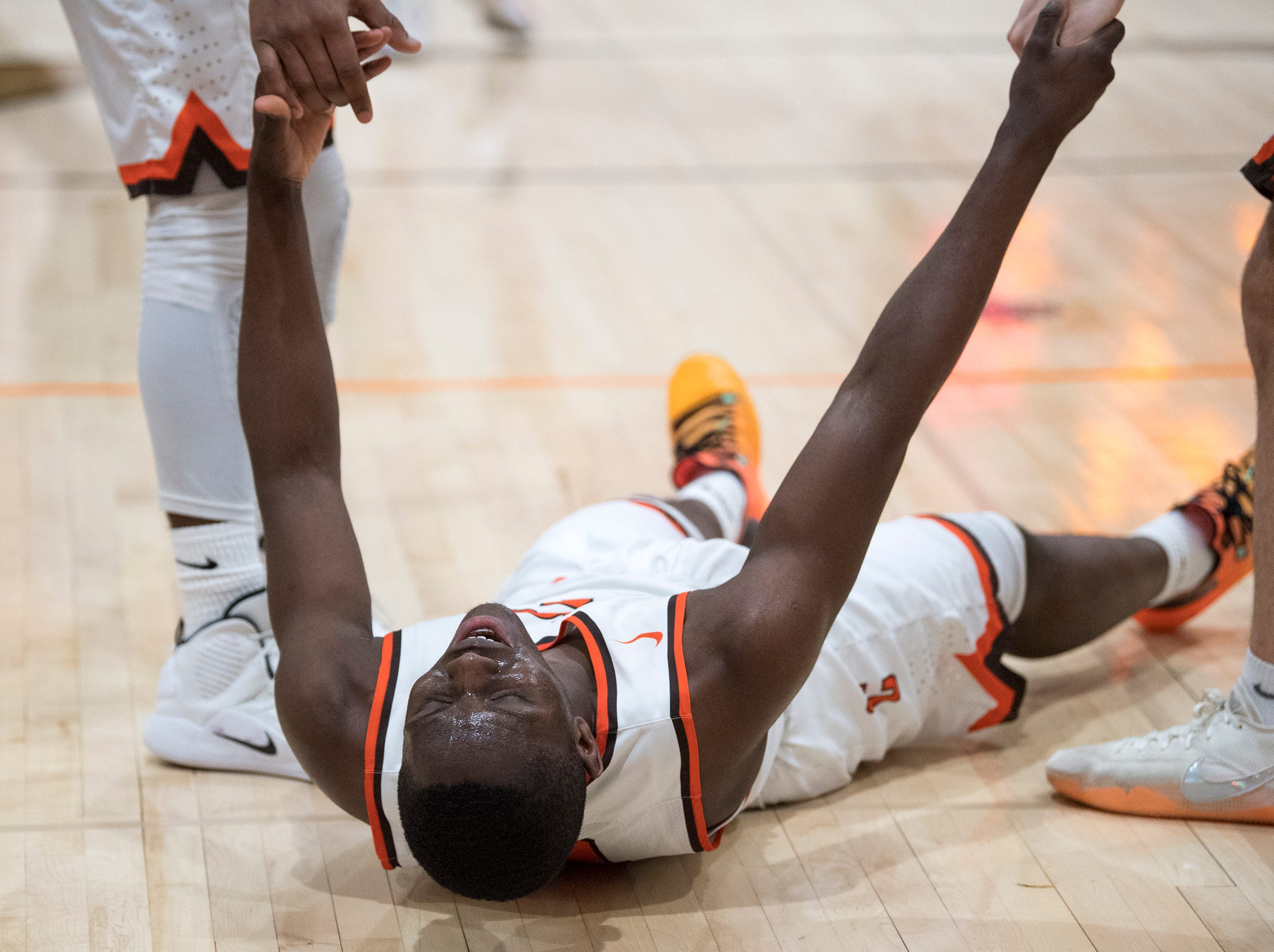 Cherokee's Olare Oladipo (4) is helped up by teammates during a game against Shawnee Monday, Feb. 25, 2019 at Cherokee High School in Marlton, N.J. Cherokee won 54-38.