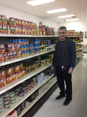 Riyad Mazahra stands in an aisle of the new Ammon Mediterranean Market, a grocery store he runs with his cousin in Cherry Hill.