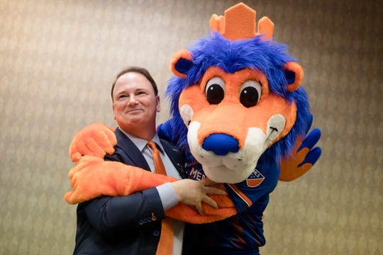 Jeff Berding, FC Cincinnati president, is embraced by the FC Cincinnati Mascot Gary The Lion during FC Cincinnati's media day on Tuesday, Feb. 26, 2019, in Cincinnati.