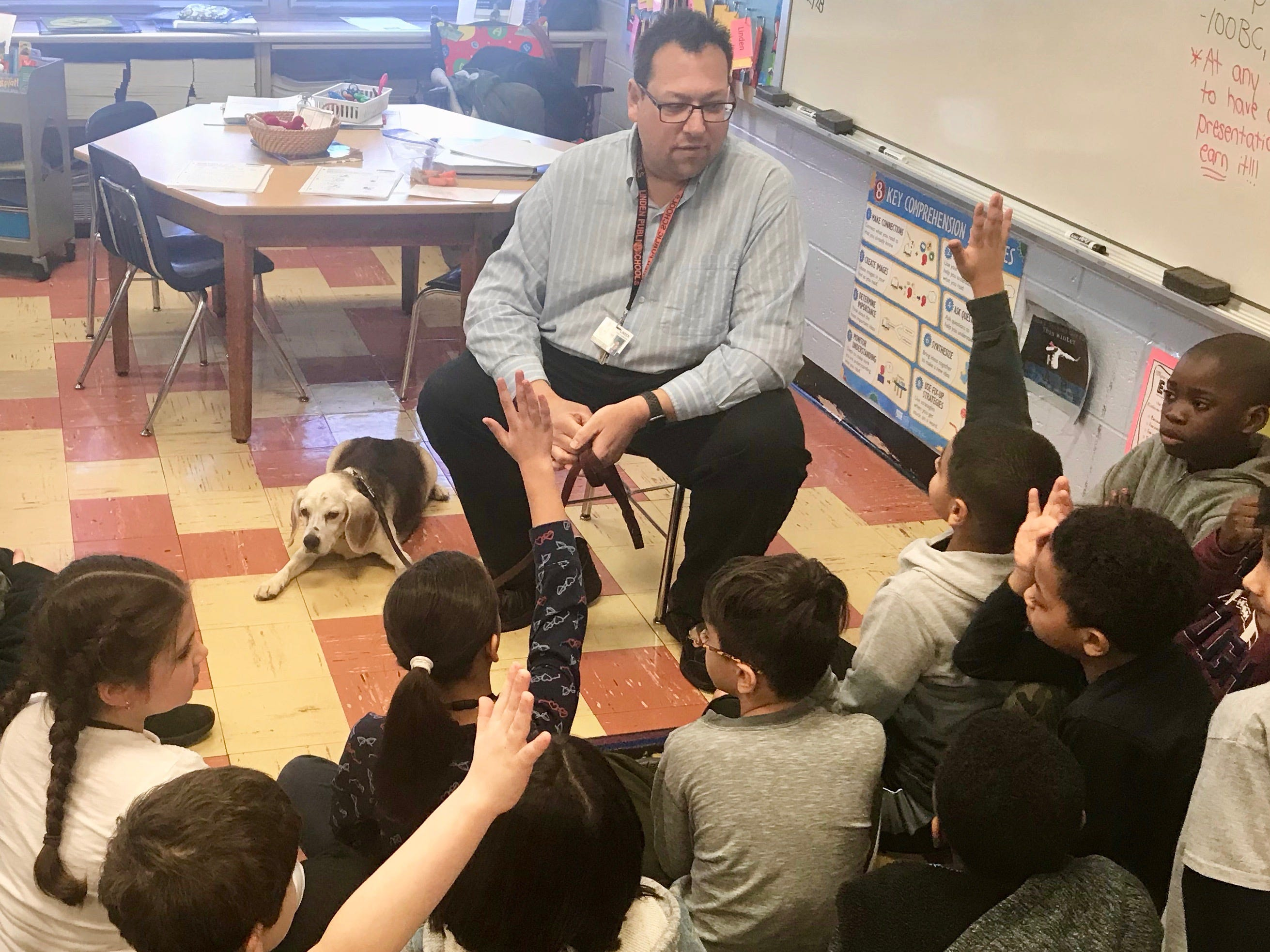 Walter Schweikardt, an elementary math coach in Linden Public Schools, tells students in Casey Mulroe's class at Deerfield School No. 9 about how he adopted Buster and how Buster became a therapy dog.