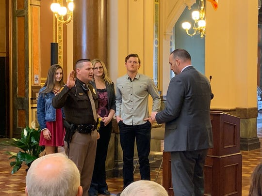 New Iowa State Patrol Col. Nathan Fulk, left, takes his oath with Department of Public Safety Commissioner Stephan K. Bayens Friday, Feb. 22, 2019, at the Iowa State Capitol during a ceremony announcing Fulk's promotion to the position. Fulk's family is  shown as well.