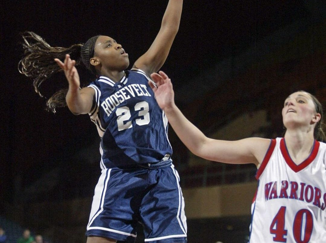 2005: Rider guard Charmaine Bell shoots two over Blair Ernst at the state girls' basketball tournament. Register file photo