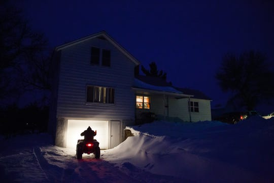 Katie Vaske parks her ATV before pulling it in the garage at home on their farm on Friday, Feb. 22, 2019, in Manchester.