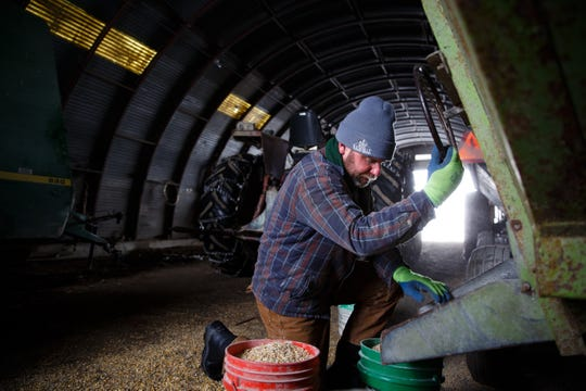 Dan Hanrahan fills buckets with feed for a few of his cattle heard on Tuesday, Feb. 26, 2019 in Cumming. Most of Hanrahan's heard is out feeding on the corn fields from last year but he said they will roll out hay bales as need and supplement with feed as well for the pregnant cows.