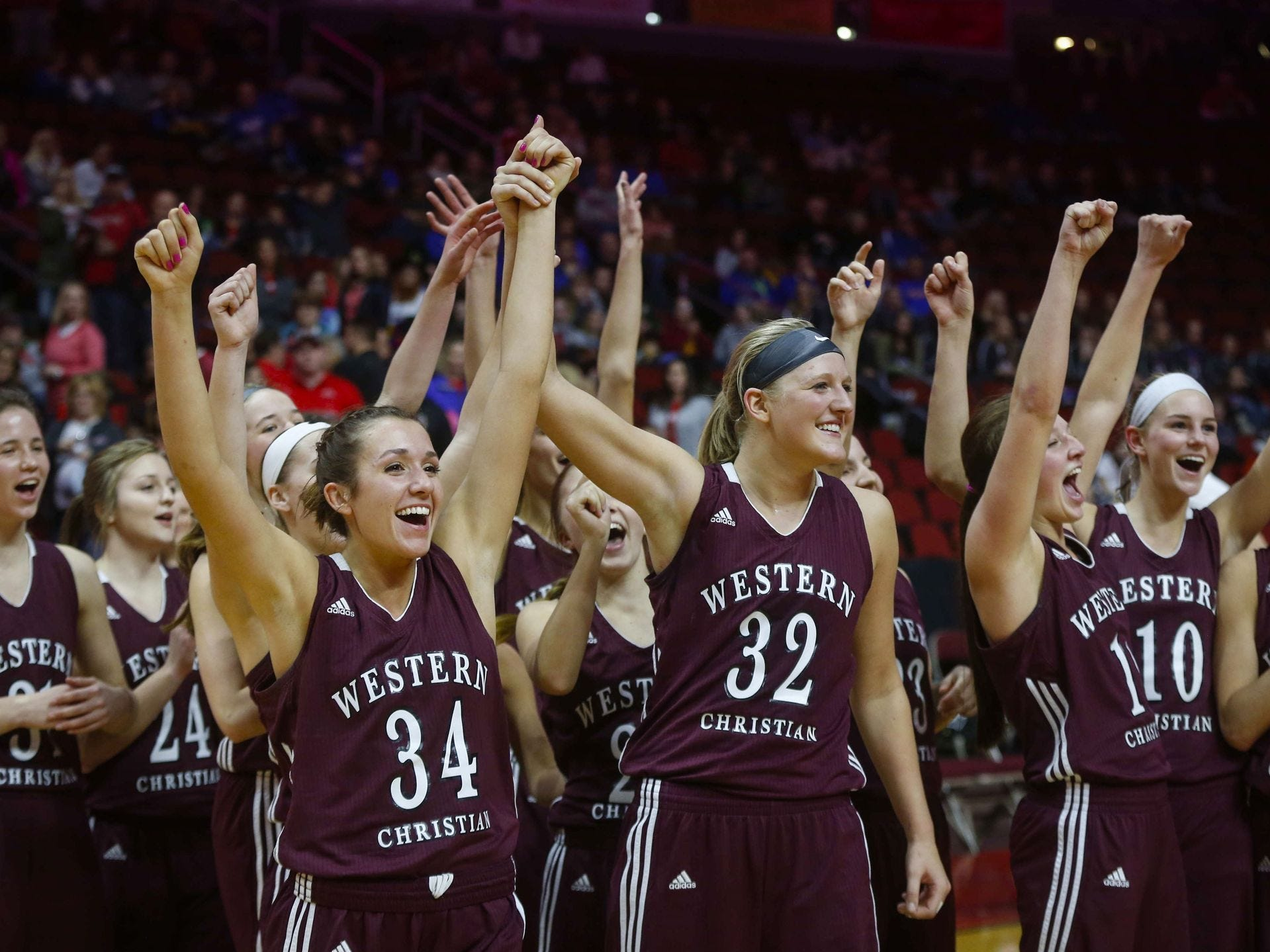Members of the Western Christian girls basketball team celebrate after beating Regina during the Iowa high school girls state basketball tournament March 2, 2017, at Wells Fargo Arena in Des Moines. Bryon Houlgrave/Register file photo