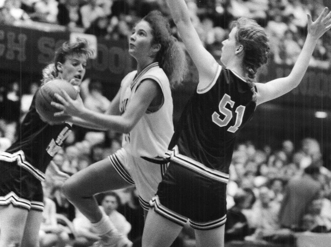 1990: Elk Horn - Kimballton's #43 Danielle Hoegh drives to the basket to score between Pomeroy - Palmer's #41 Heidi Hanson and #51 Amy Heidi. Register file photo