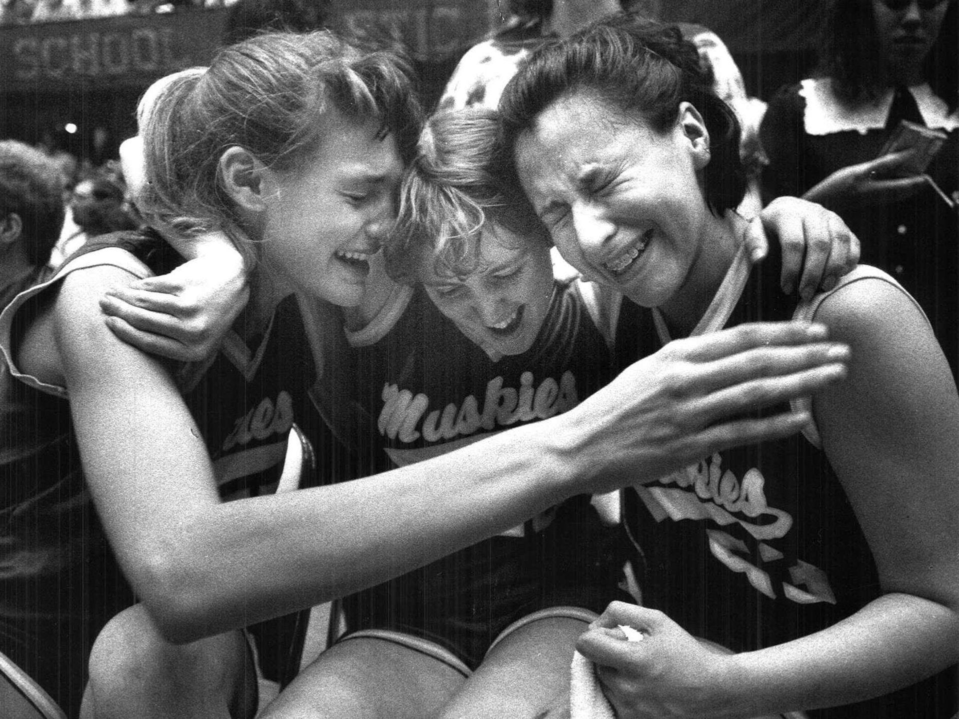 1989: Muscatine players (from left) Jenny Noll, Joy Movick and Marivel Rivera celebrate after their win. Register file photo