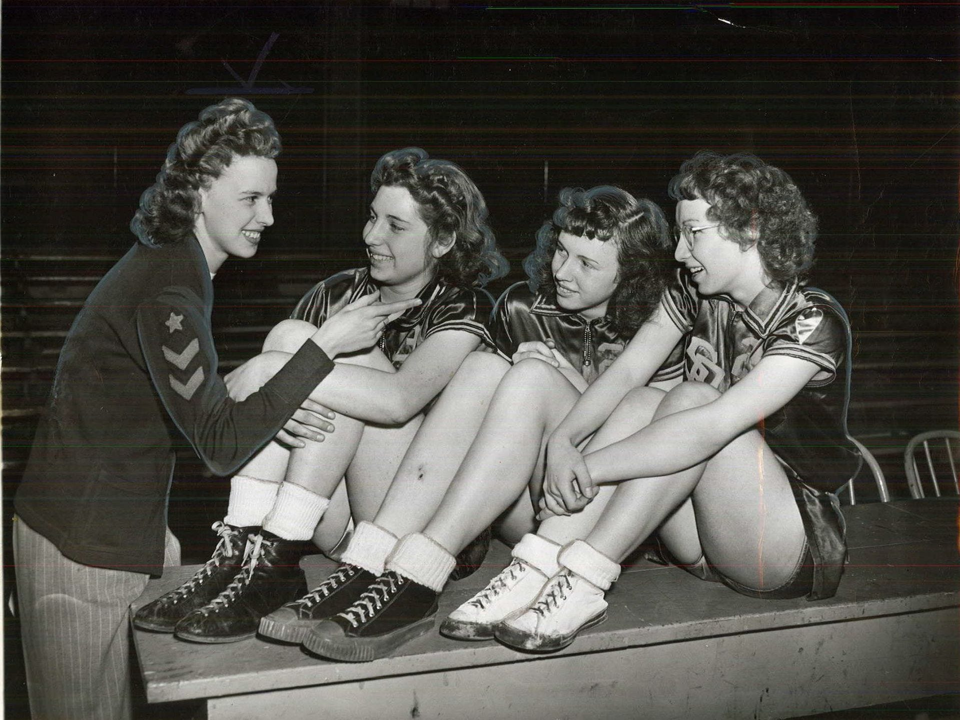 1946: Ivy Mae Gast, who played for Steamboat Rock in 1944, talks to members of the 1946 team during the state girlsÕ basketball tournament. Register file photo
