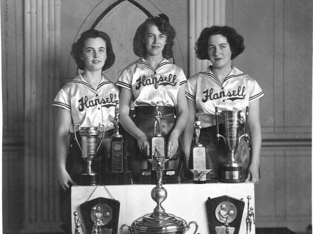 1941: Hansell High School players, left to right, Janice Harrison, Bette Oswood and Helen Van Houten pose with some of their state tournament trophies. Register file photo