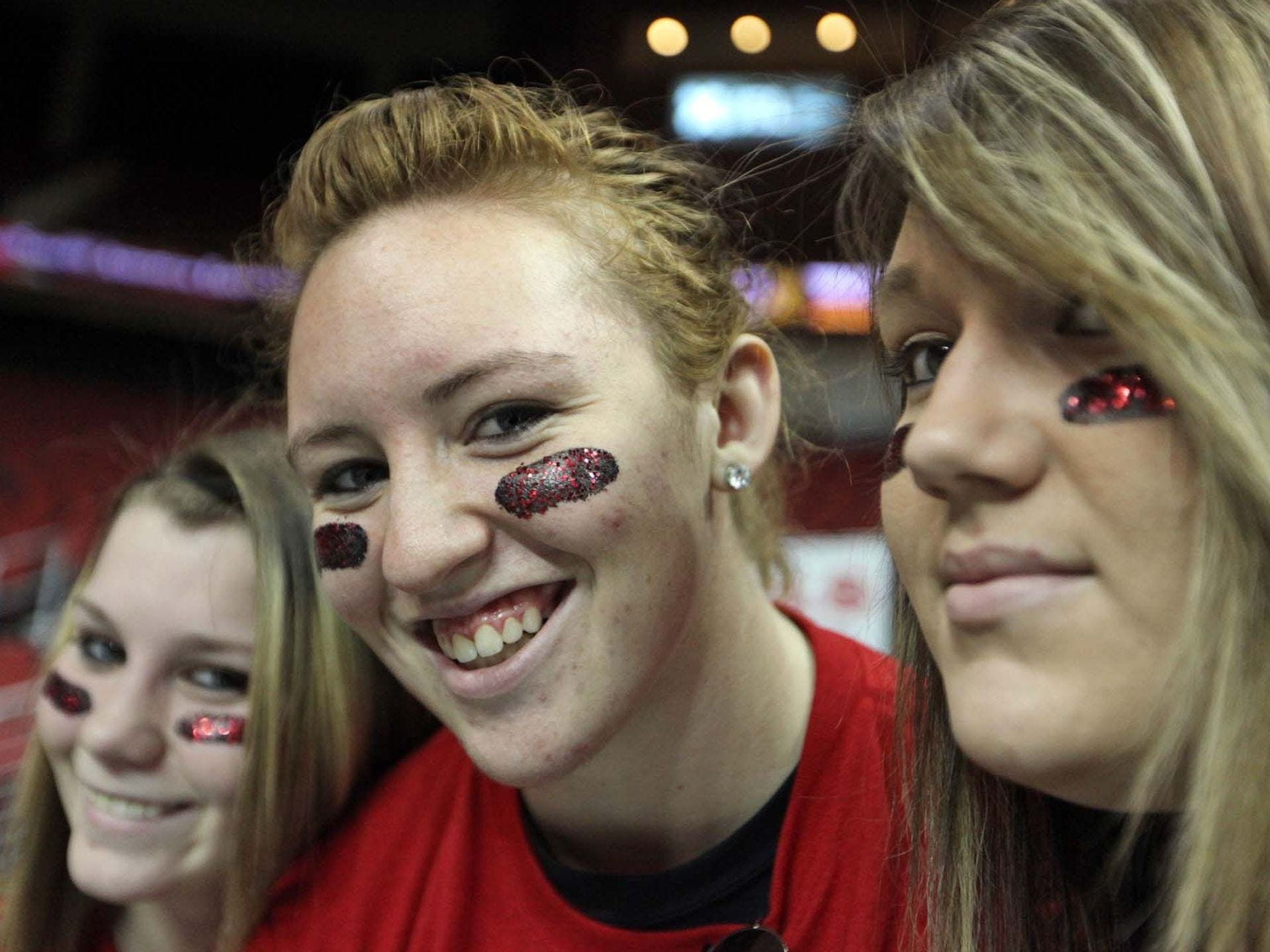2011: East High juniors (left to riight) Taylor Anderson, Jessica Grochala and Nicole Underwood sport their own creation (actually thought of first by Nicole) -- black acrylic paint with a layer of red glitter as face decoration -- before a 4-A semifinal round game. Register file photo