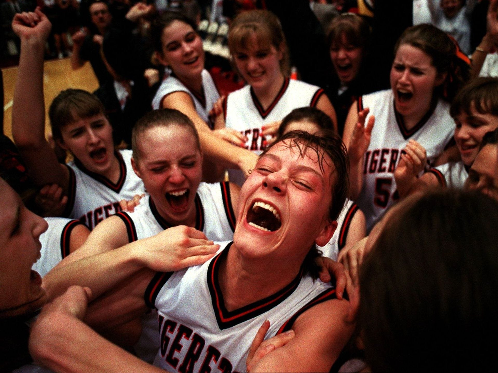 1996: Sara Stribe (center looking up) celebrates with Carroll teammates after she was named captain of the all-tournament team and after Carroll defeated Vinton-Shellsburg for Class 3A championship at the state girl's basketball tournament. Register file photo