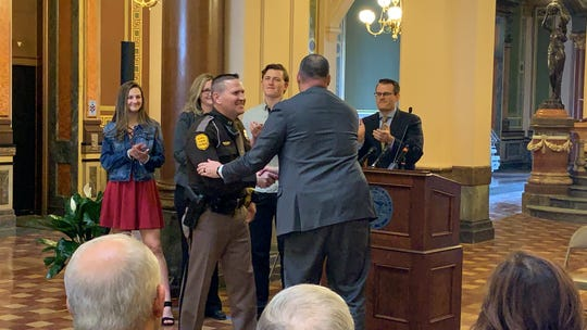 New Iowa State Patrol Col. Nathan Fulk, left, shakes the hand of Department of Public Safety Commissioner Stephan K. Bayens Friday, Feb. 22, 2019, at the Iowa State Capitol during a ceremony announcing Fulk's promotion to the position. Lt. Gov. Adam Gregg, background far right, and Fulk's family are shown as well.