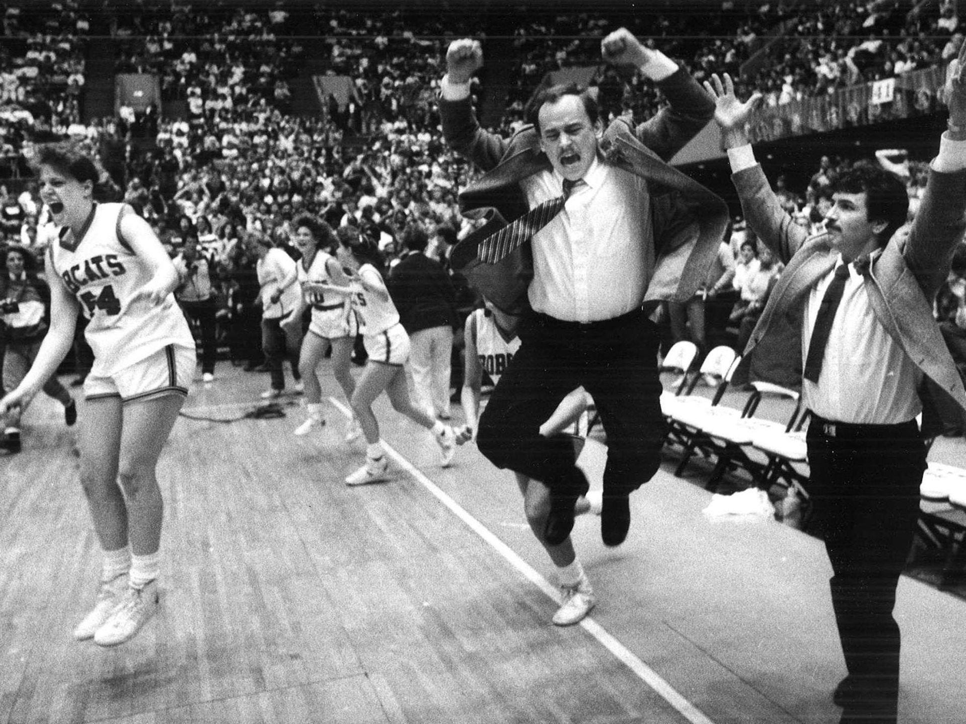 1987: Western Dubuque player Kim Kluesner (54), assistant coach Jim Demmer and coach Bill Hoefer celebrate after their team victory. Register file photo