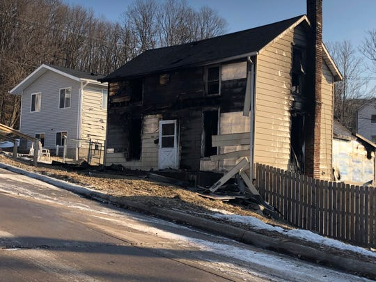 A heavily damaged a two-story house by a fire is seen Tuesday, Feb. 26, 2019, in Muscatine, Iowa.  Firefighters dispatched Monday found flames coming from several doors and windows, the Muscatine Fire Department said. Three bodies were found inside the home.
