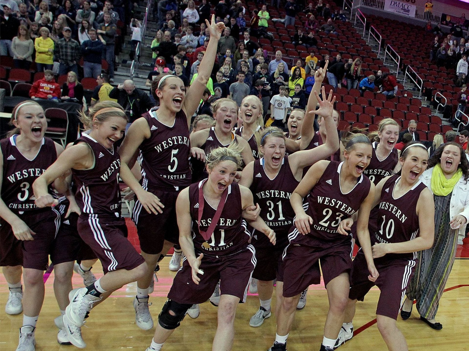 2014: Western Christian (Hull) players charge the trophy after their win over Hudson in the Class 2-A championship final at the state girls' basketball tournament. Register file photo