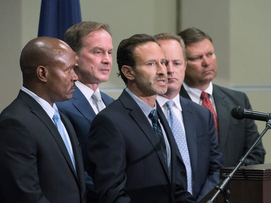 Special Assistant Attorney General Noah Hall, center, speaks during a  June 2016 press conference about about the Flint water crisis investigation.