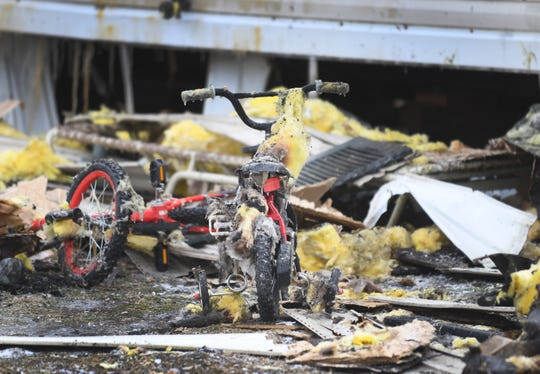 Several small bikes with training wheels sit amid the debris of the fire.