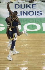 Michigan's Rumeal Robinson leaps into the arms of teammate Glen Rice as the Wolverines win the NCAA basketball championship in 1989.