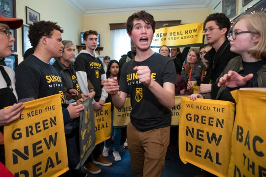 Jeremy Ornstein of Watertown, Mass., center, cheers on fellow environmental activists as they occupy the office of Rep. Steny Hoyer, D-Md., the incoming majority leader, as they try to pressure Democratic support for a sweeping agenda to fight climate change, on Capitol Hill in Washington, Monday, Dec. 10, 2018.