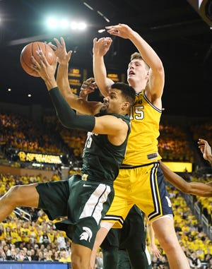 Michigan State's Kenny Goins pulls down a rebound under Michigan's Jon Teske in the second half Sunday in Ann Arbor.