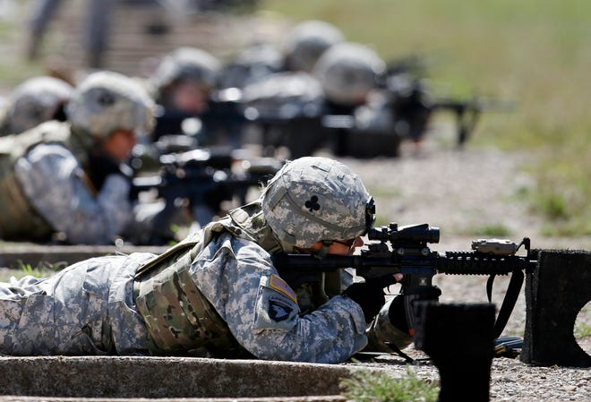 FILE - In this Sept. 18, 2012 file photo, female soldiers from 1st Brigade Combat Team, 101st Airborne Division train on a firing range while testing new body armor in Fort Campbell, Ky. Congress is on the verge of ordering young women to register for a military draft for the first time in history, touching off outrage among social conservatives who fear the move is another step toward blurring gender lines.
