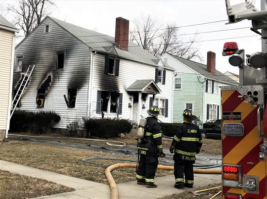 Elmira firefighters survey the damage Tuesday afternoon after battling a blaze on the city's Southside.